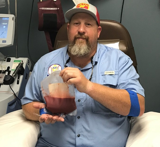 Jeremiah after donating, holding a bag of his blood stem cells